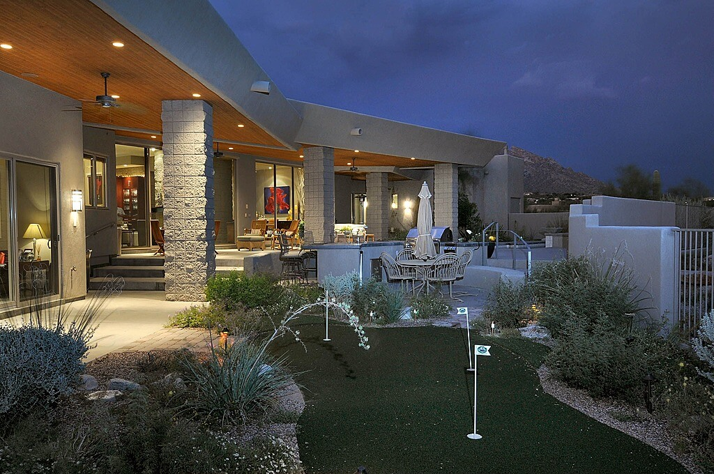 Compact custom artificial green embedded in Southwest style garden, steps away from expansive outdoor seating space of this thoroughly modern home.