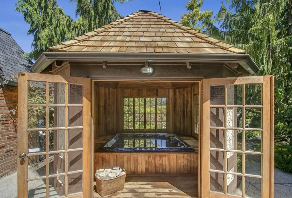 Octagonal bath house sits on patio, holding a large jacuzzi on raised wooden frame beneath its natural wood shingle roof.