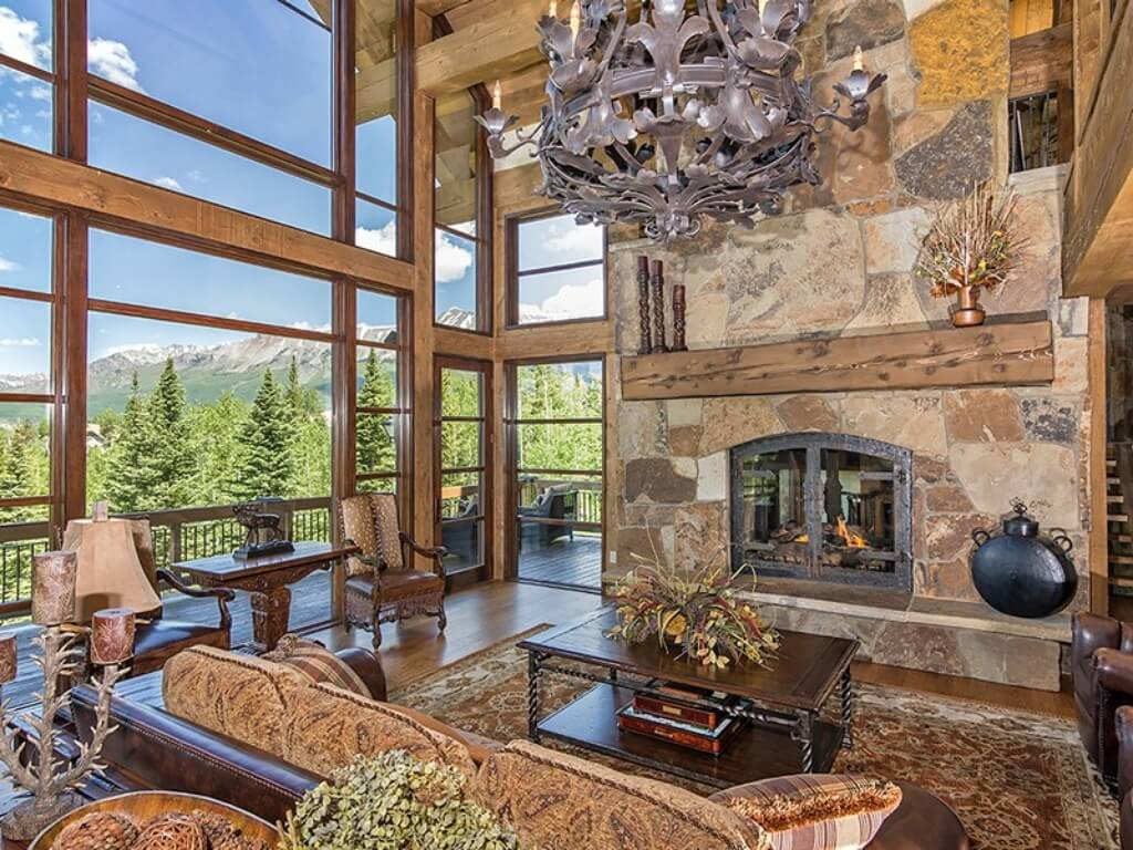 Here's the living room seen lit by natural light through the massive floor to ceiling windows at left. Framed in natural wood with exposed beams overhead, the exterior glass wall affords views of the surrounding mountain range.