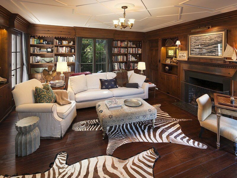 Casual living room design with dark wood flooring, fireplace, white furniture, built in bookshelves, wood paneling and two zebra skins on the floor