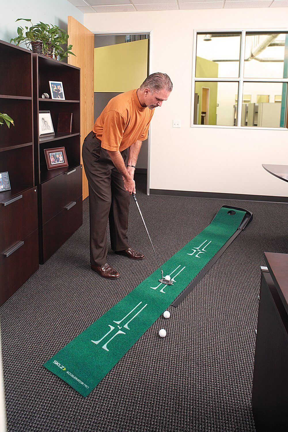 This indoor putting green is a more traditional example, with rolled-out surface locking into a simple raised plastic hole and ball return.