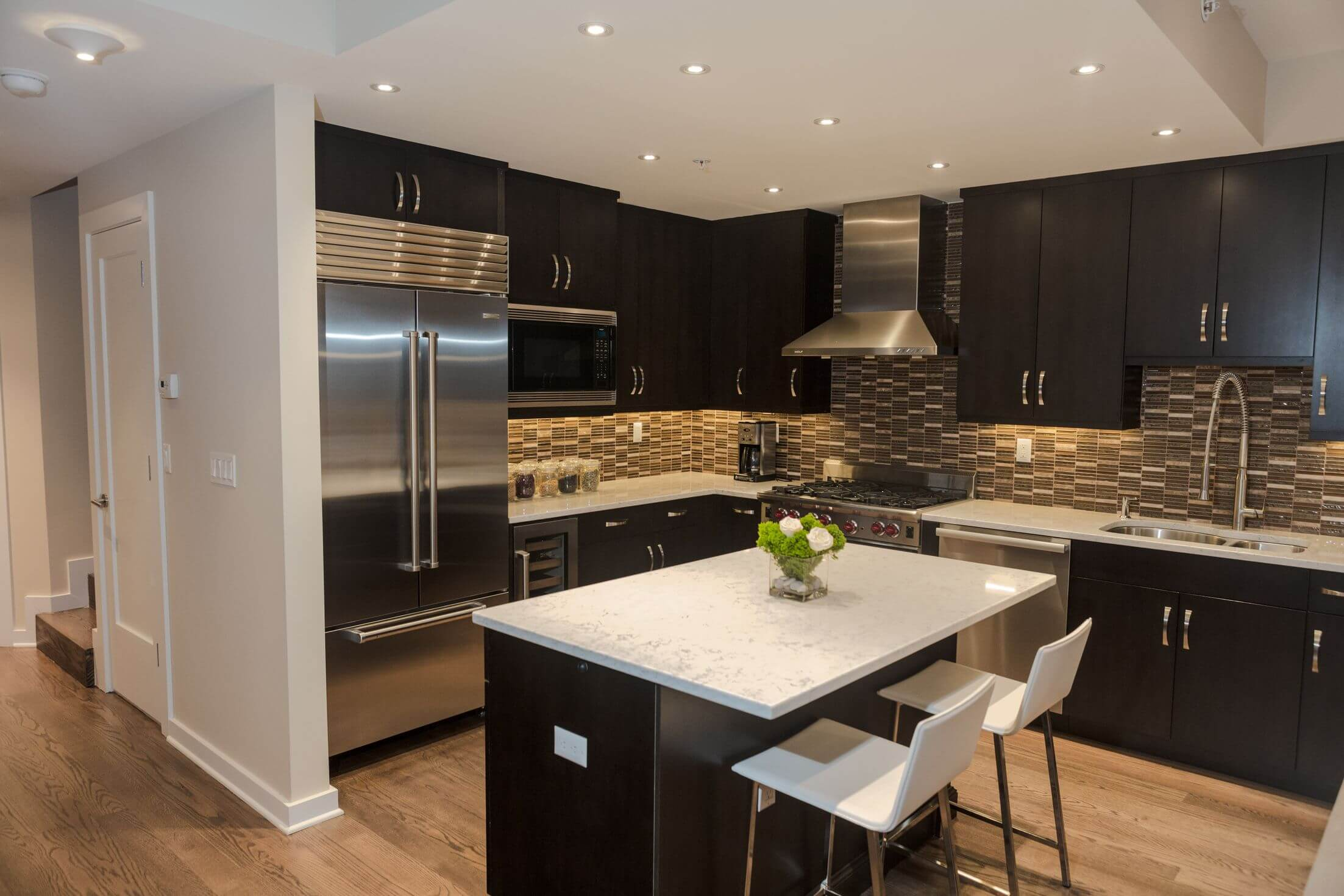 Black wood cabinetry and island contrast with patterned tile backsplash, white marble countertops, and light natural hardwood flooring.