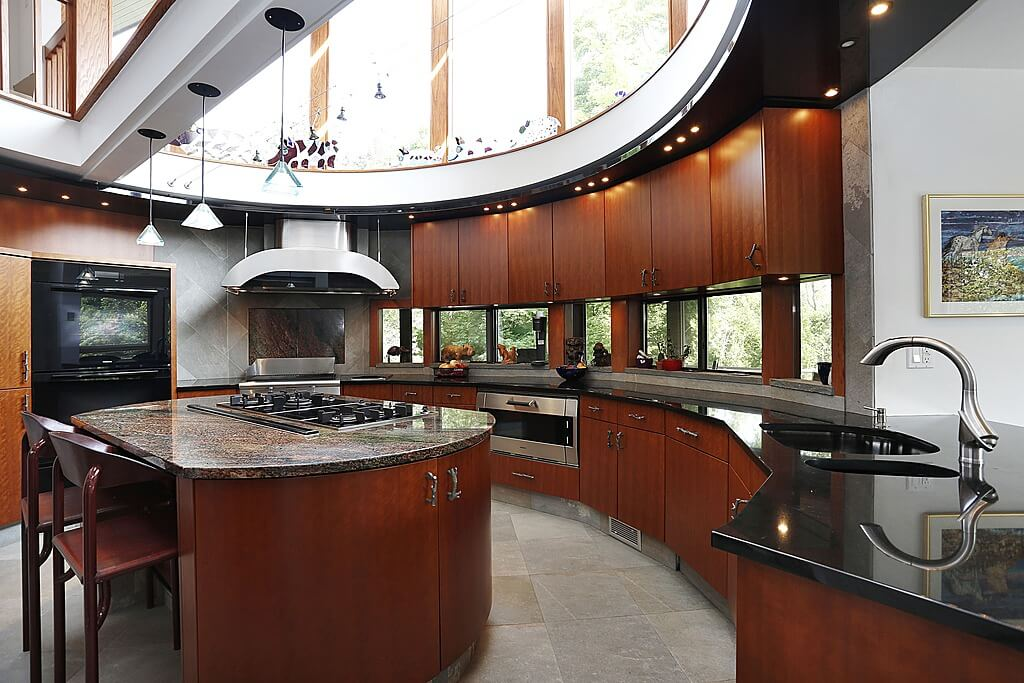 Unique, modern sunlit kitchen features open sky-light ceiling and oval design. Dark natural wood cabinetry and island support dark marble countertops over grey stone flooring.