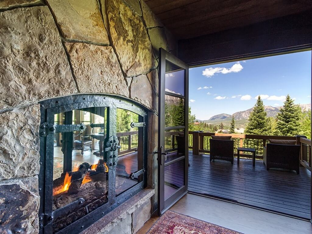 This view from the living room showcases wrought iron, glass door fireplace and open view to outdoors through large glass French doors to balcony.