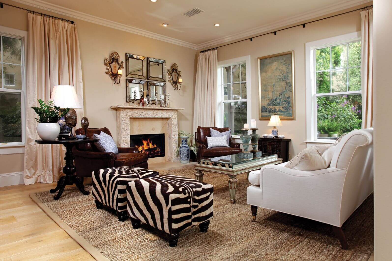 Larger formal living room incorporating zebra print with two identical zebra print ottomans off to the side of the main seating which includes a white sofa, two ruby red armchairs, ornate coffee table all surrounding an ornate fireplace.