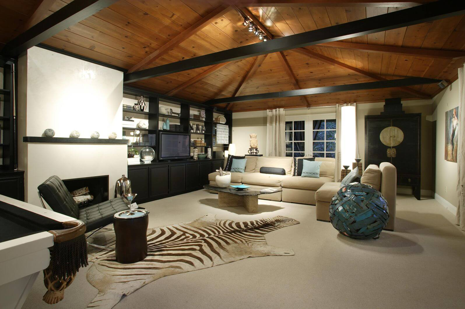 Spacious casual living room with beige armless sofa and armchair, modern black armless chair and large zebra skin on the floor spanning much of the room