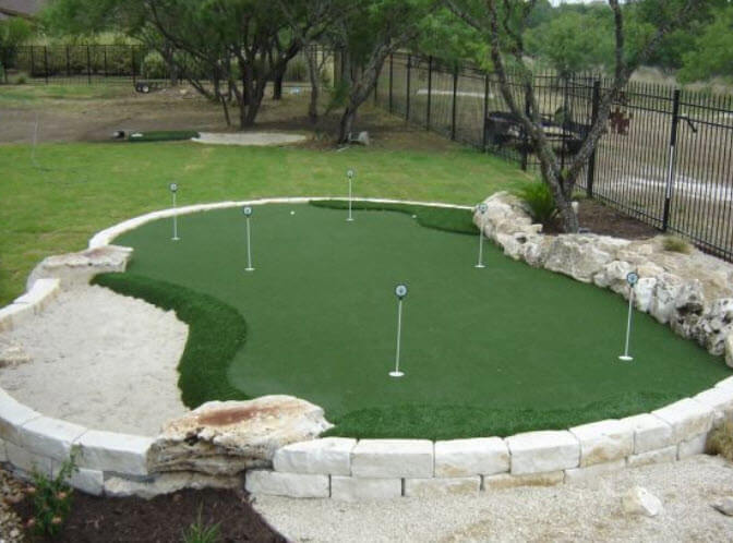 Unique green situated in raised stone barrier, integrating natural stone features on border. Features multiple holes and approaches, plus full sand trap.