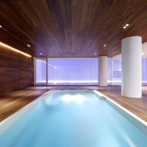 Modern indoor pool opening to outdoor patio
