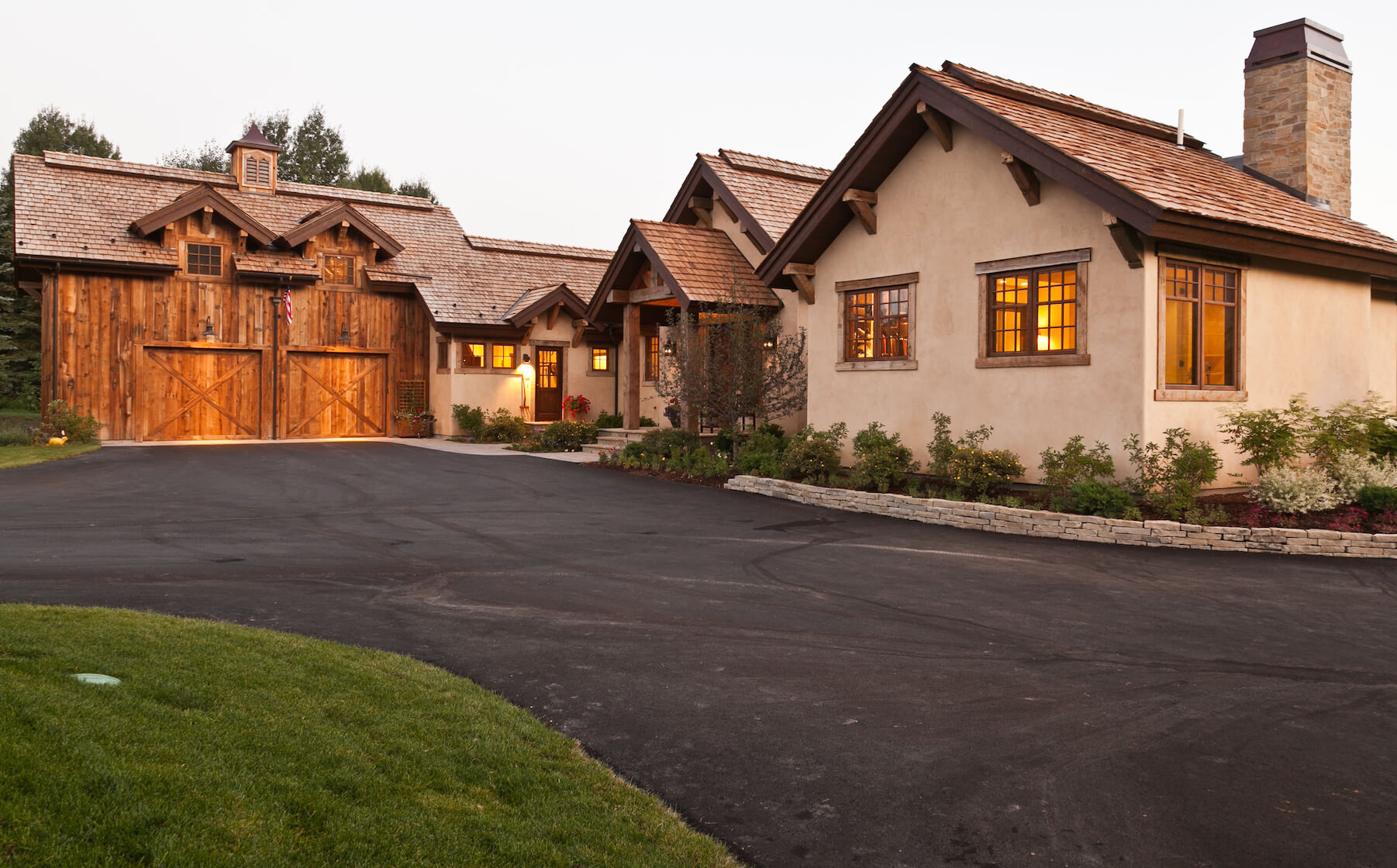 Full view from the driveway, highlighting attached garage made of reclaimed old barn wood, and beige stucco exterior with exposed beams under roof.