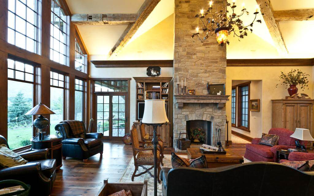 Immense great room sits under soaring exposed beams and centers around full height stone fireplace surround. Natural wood flooring and window and door surrounds are complimented by dark leather furniture and lit by large, ornate chandelier.