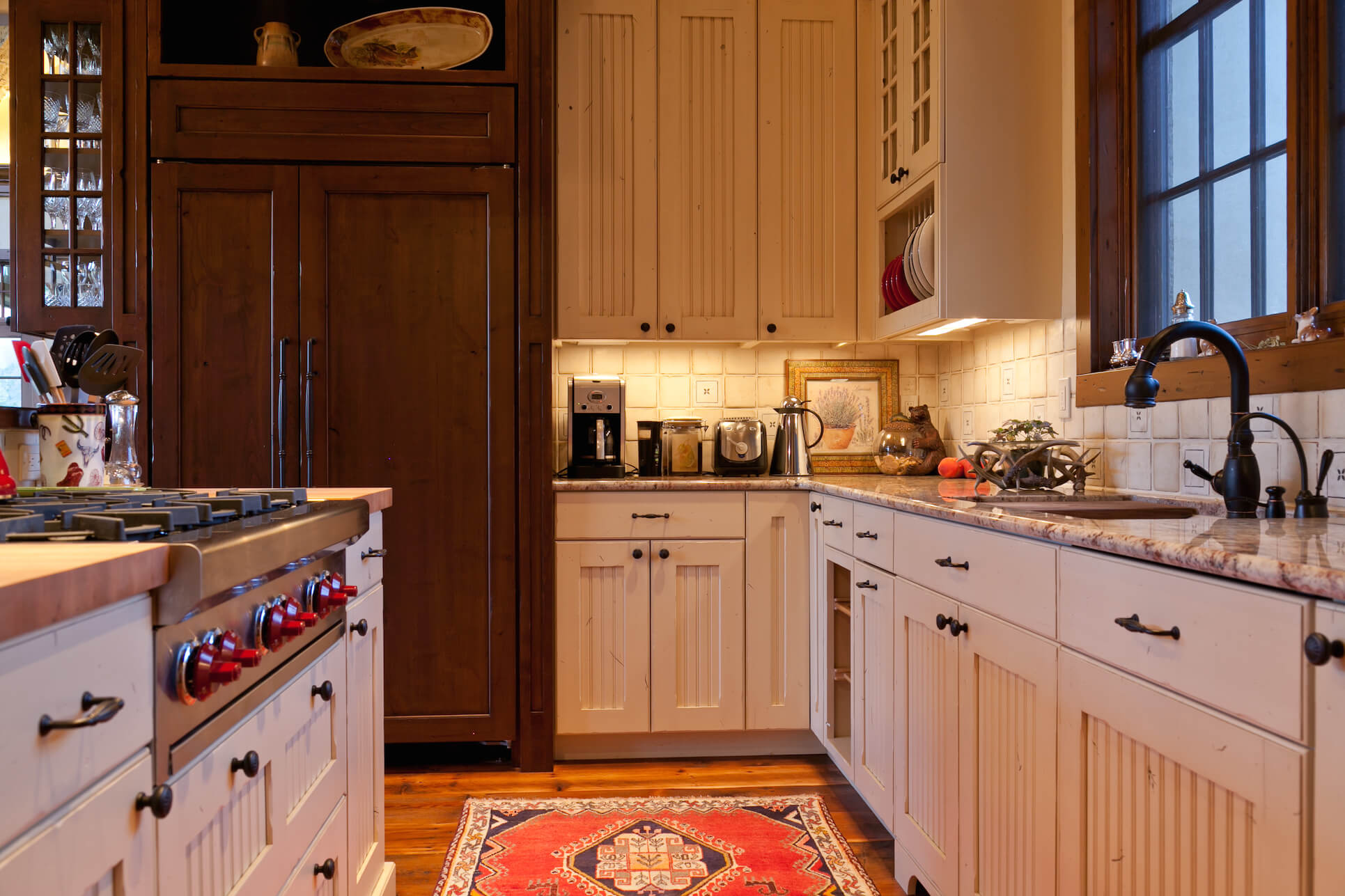 Low view of the kitchen, highlighting warm wood tones, patterned tile backsplash, and black cabinetry hardware.