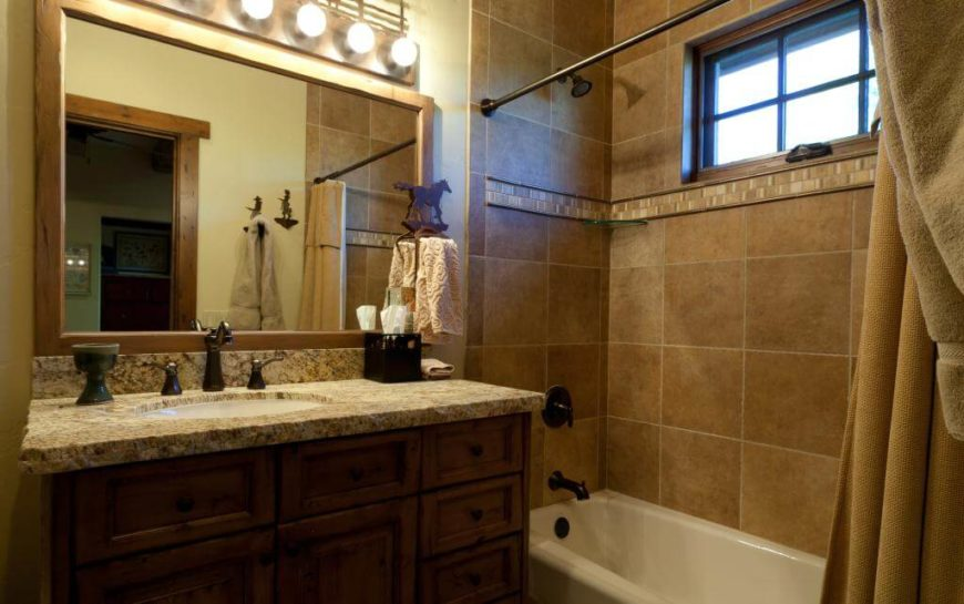Bathroom continues the desert style color scheme with shower tiling and natural wood mirror surround and cabinetry.