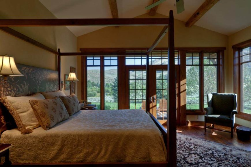 Primary bedroom holds large corner view of outdoors, courtesy of floor to ceiling windows on external walls. Natural wood framing, flooring, and bed frame contrast with light desert toned walls under vaulted ceiling with exposed beams.