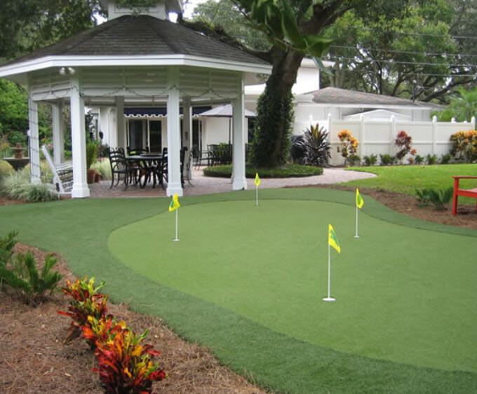 Gently sloped custom green here flows from white wood gazebo on brick patio in the backyard of this large white home.