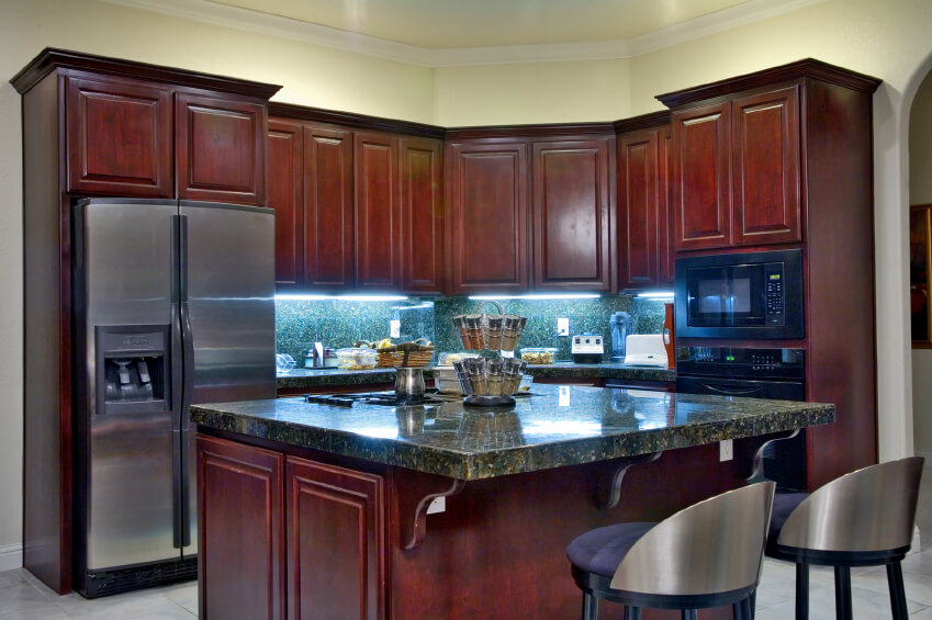 Here's a corner kitchen decked out in dark cherry wood with dark forest green marble countertops and matching backsplash over white tile flooring.