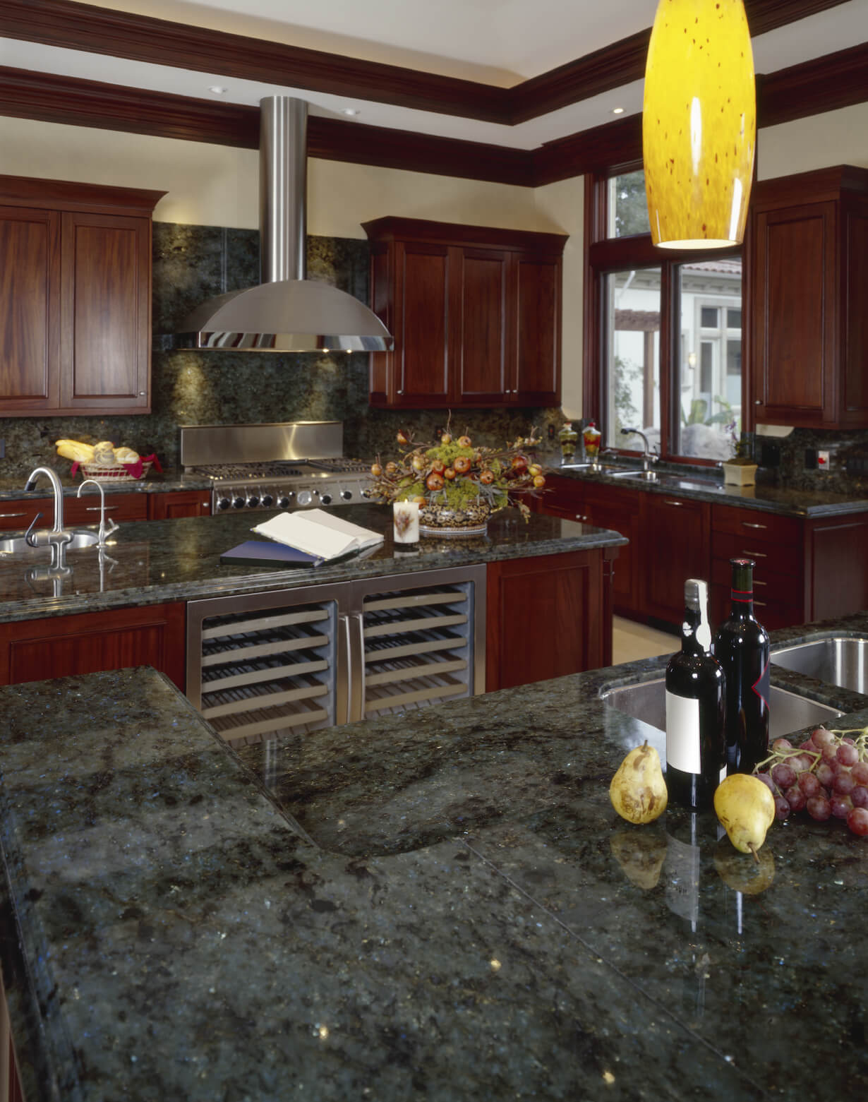 Rich dark green marble countertops and dark cherry wood fill this luxurious kitchen featuring brushed aluminum appliances and island with built-in wine cooler.