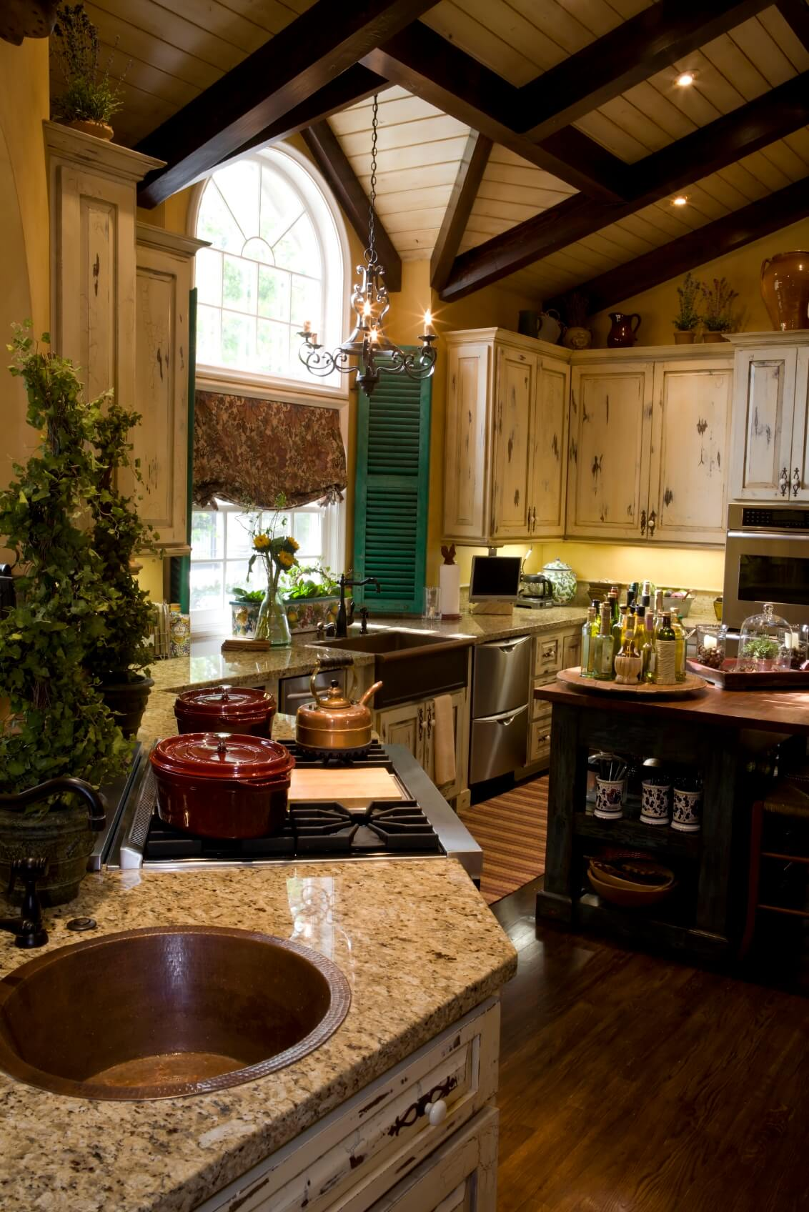 "A menagerie of detail is stuffed into this cozy kitchen, including exposed wood beam ceiling, beige marble countertops, hardwood flooring, black wood island, and ""aged"" painted light wood cabinetry, accented by bright green shutters."