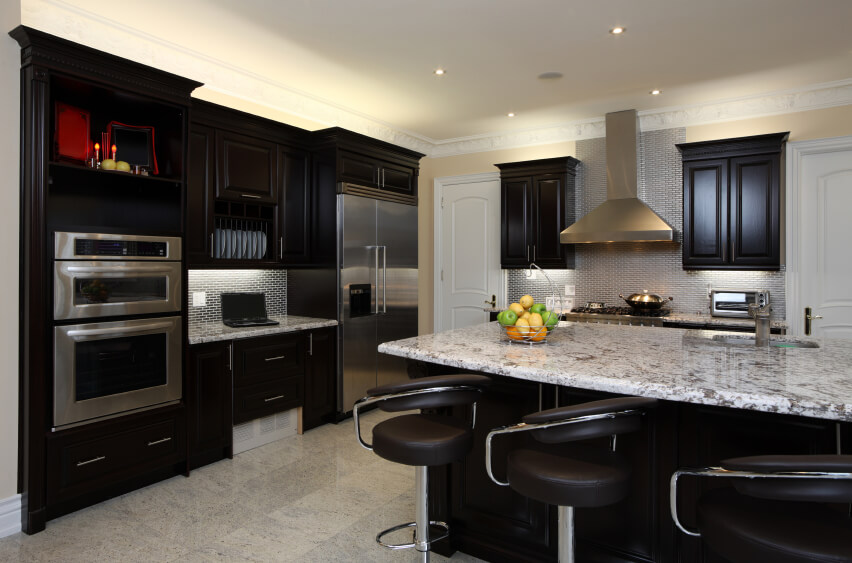 Kitchen is great example of high contrast between dark toned wood cabinetry and light marble surfaces, with large island featuring dining space, plus micro-brick tile backsplash.