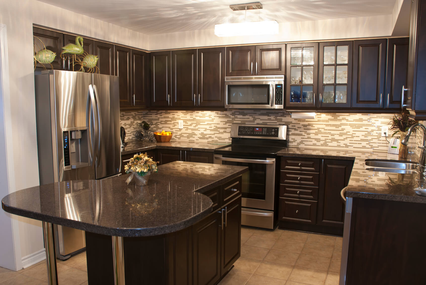 Cozy kitchen is stuffed with dark wood cabinetry, with brushed metal hardware. Black marble countertops and patterned tile backsplash, plus aluminum appliances, add contrast.