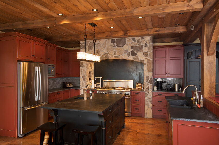 Here's another lush, rustic styled kitchen, with dark red stained cabinetry under black marble countertops. Exposed beams and natural hardwood flooring complete the look.