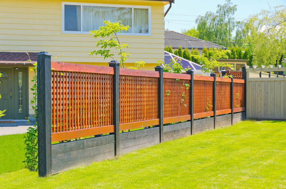 Modern lattice fence comprised of black stained wood posts and base ...