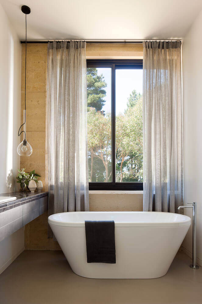 Bathroom features white pedestal bathtub next to windows, with continuation of the kitchen tiles on counter to the left.