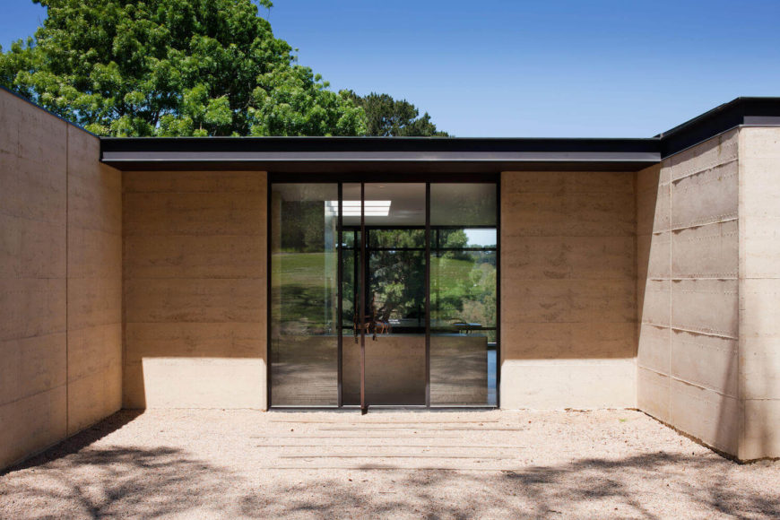 This central outdoor view highlights the rammed earth construction and floor to ceiling glass, combining for structural efficiency.