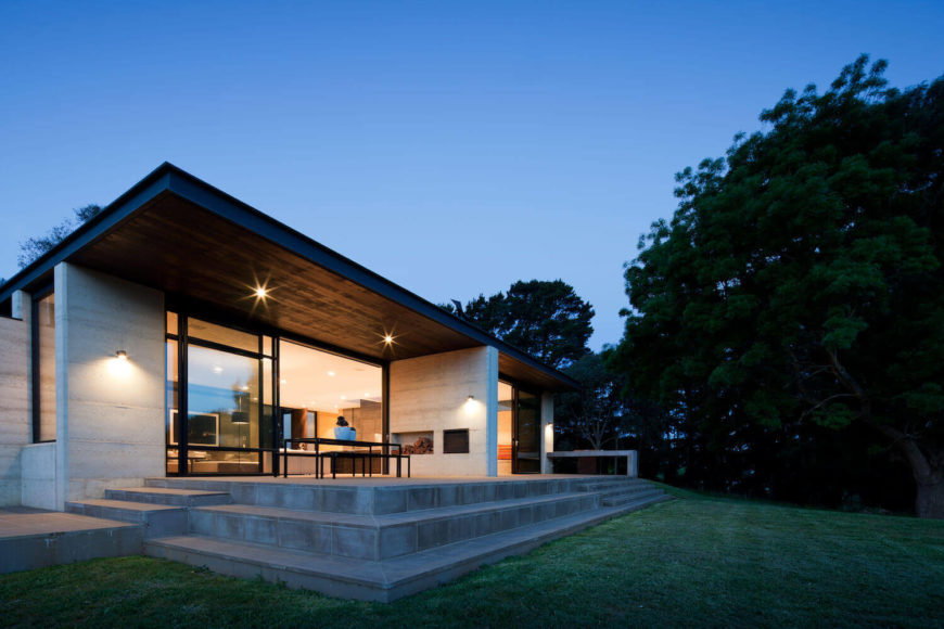 The foundation extends onto this tiered patio, with steps leading down to gently sloping lawn. Floor to ceiling glass under the large eaves allow indirect lighting throughout.