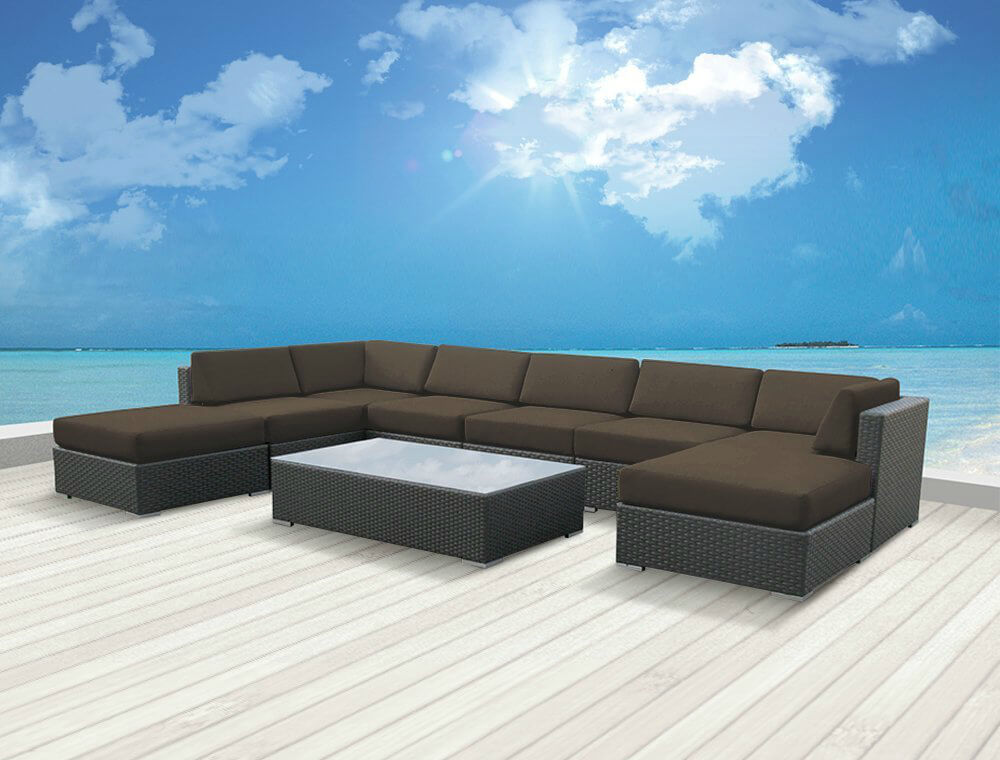 Super lengthy wicker sectional features deep seating courtesy of thick padded chocolate cushions, plus chaise lounge and detached ottoman piece, wrapped around large, low-slung glass top coffee table.