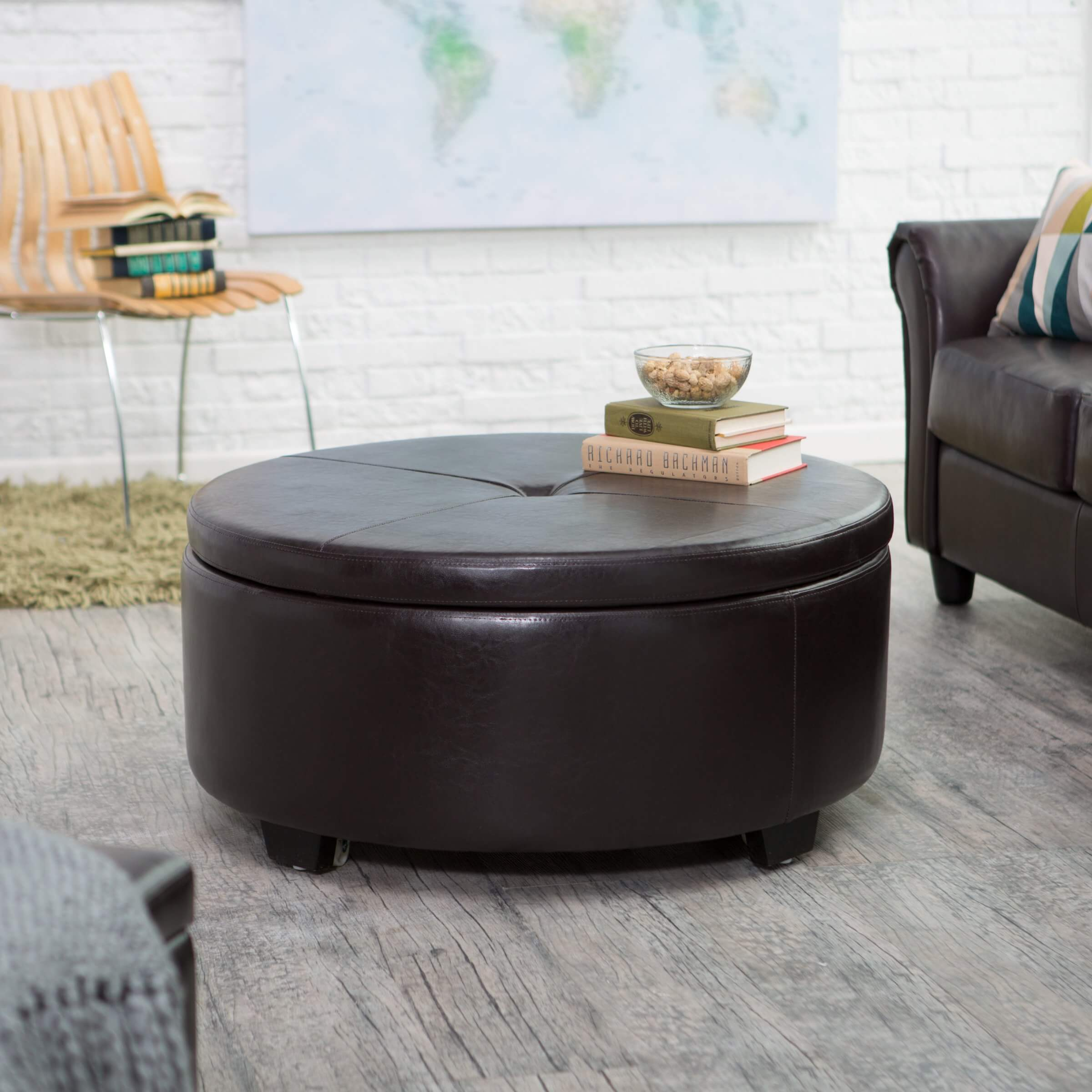 Large circular bonded leather and wood ottoman has flip-top button tufted lid featuring full coffee table surface on opposite side, concealing large interior storage space.
