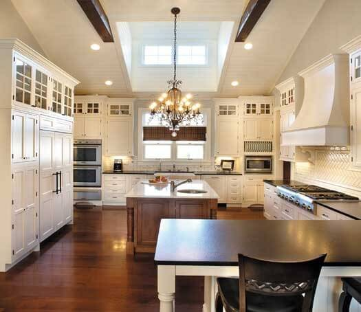Spacious white kitchen with huge skylight flooding the space with plenty of natural light. Kitchen includes peninsular, double oven, extensive storage and large island with sink.