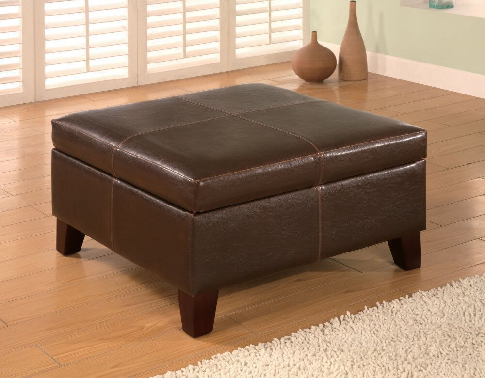 This large square ottoman comes in rich brown leather-feel vinyl and hinges open to reveal storage within, supported by tapered natural wood legs.