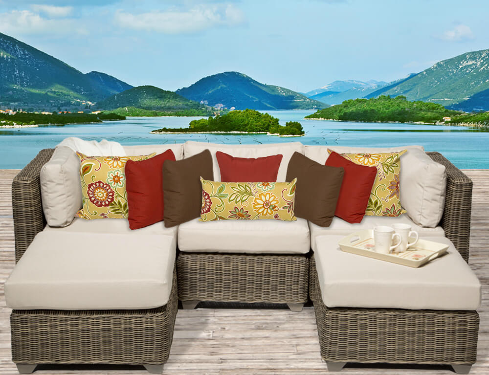 Lighter toned resin wicker body on this patio sectional holds thick light beige cushioning, with an array of colorful throw pillows on top. Twin ottomans again act as chaise lounges bookending the piece.