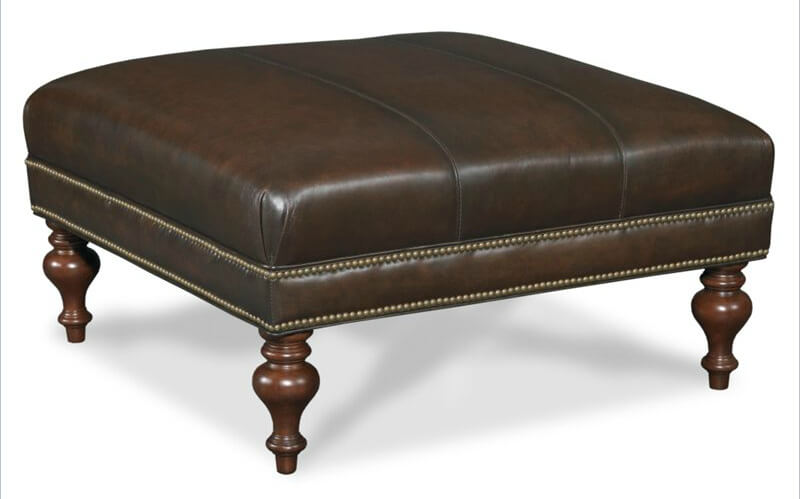Brown leather stuffed cushion ottoman stands with nail head trim over carved wood arrow feet, from Hooker Furniture.