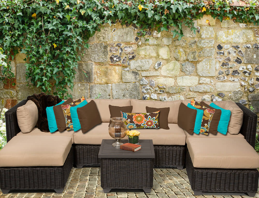 This dark brown and mocha patio sectional features twin ottomans doubling as chaise lounges, flanking a hard-topped, matching coffee table segment.
