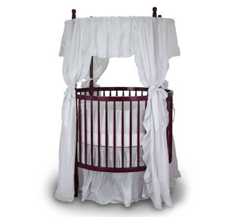This round crib is crafted in cherry wood, with fixed sides for enhanced stability. Included mattress can be adjusted to four different heights. Included feet casters have locking mechanism for safety and mobility.