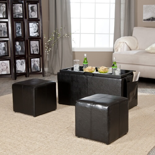 Dark leather bench ottoman features reversible cushion top with tray table, concealing interior storage and two smaller cube ottomans. Courtesy of Linon Home Decor Products.