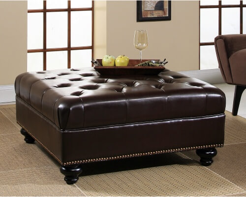 Button tufted and nail head trimmed leather upholstery covers this cushioned ottoman from Abbyson.