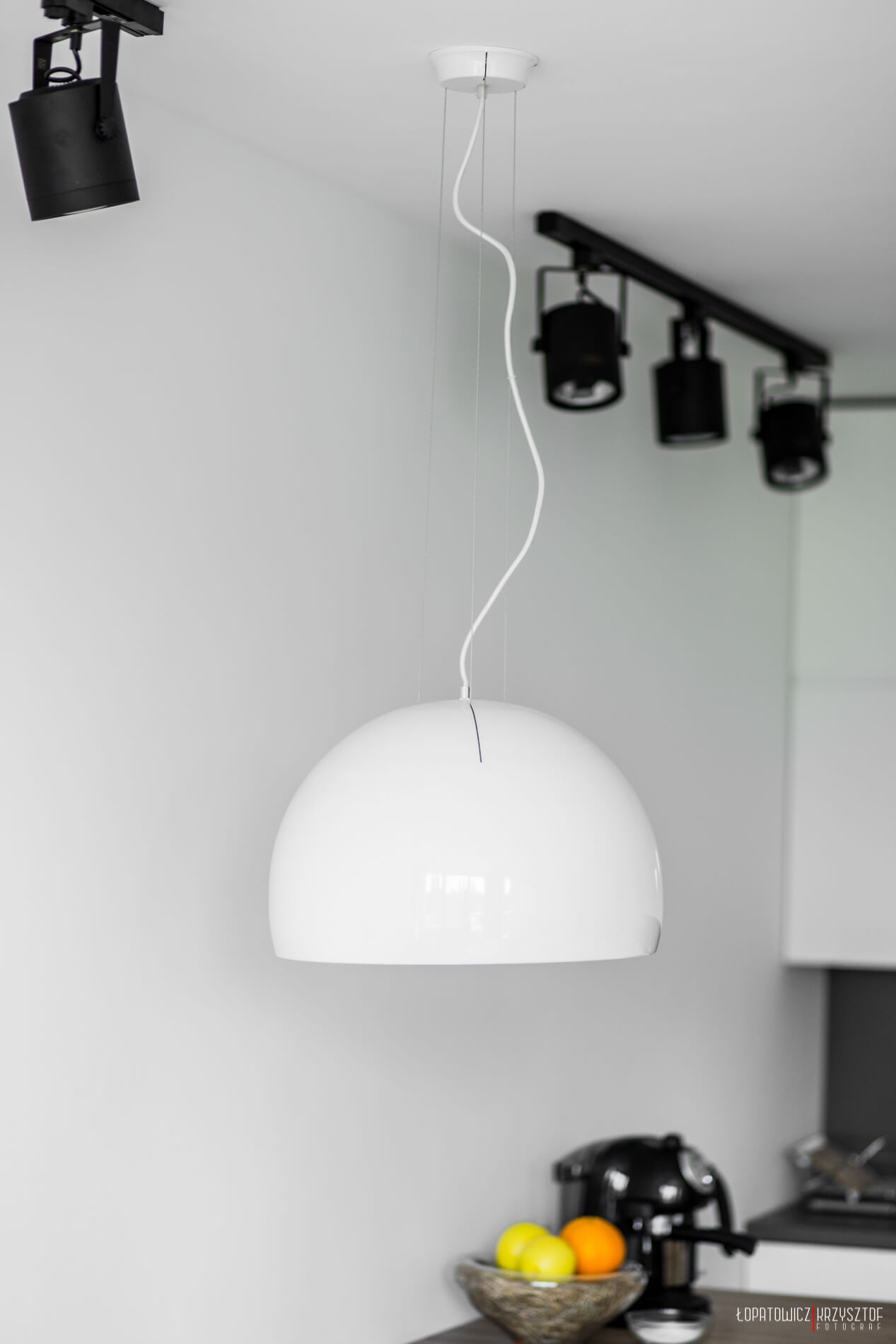 The second unique light fixture in the open space is a hemispherical white dome chandelier, hung above the dining table.