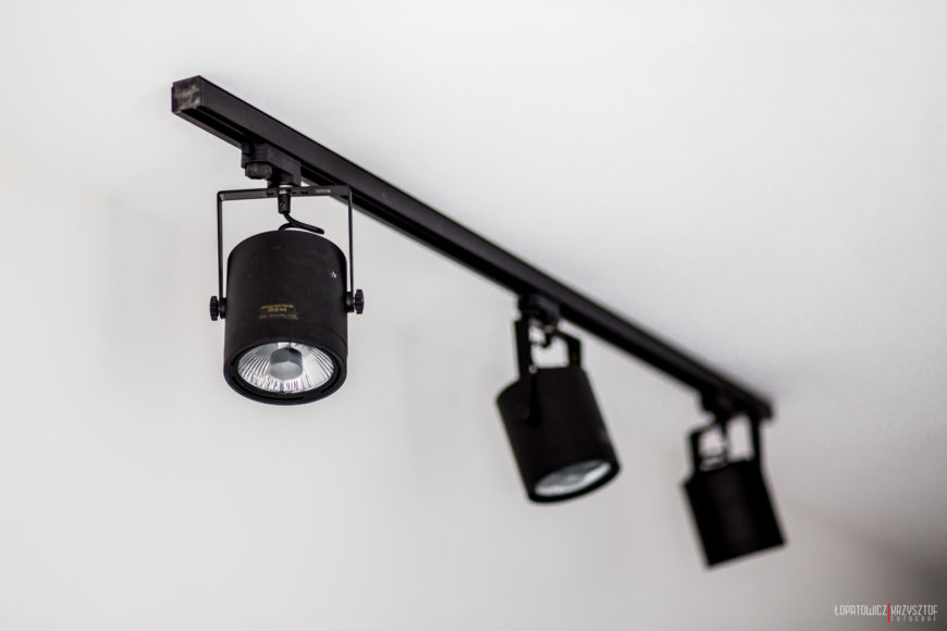 Black canister track lighting that spans the large, open living and kitchen space.