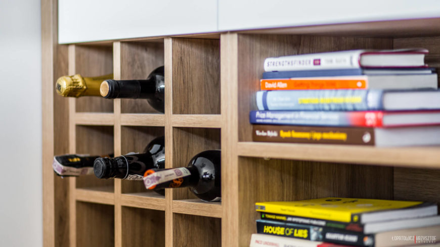 Kitchen island features built-in wine rack next to book shelves, in natural stained wood.