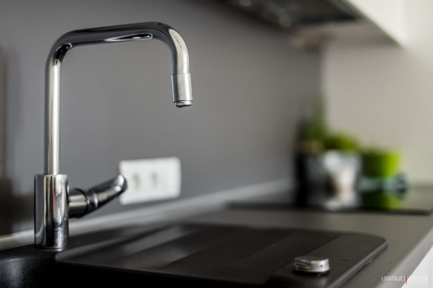 Kitchen plumbing includes this chromed faucet and matte-black basin sink.