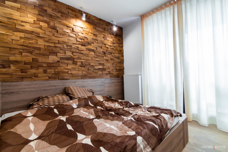The bedroom features large wood frame bed, more floor to ceiling exterior glass for natural light, and unique wood-brick wall surface illuminated by focused light sources.