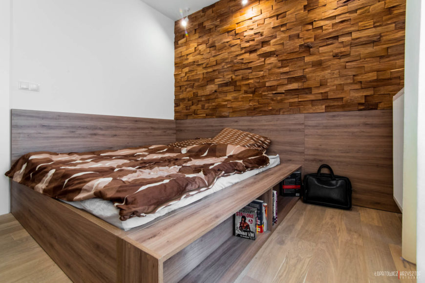 Bedroom is awash in natural wood, with bed frame material mirrored on lower all detail, and concealing useful shelving.