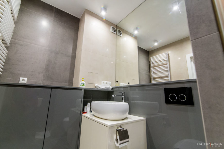Bathroom features ultra-modern look with minimalist, glossy surfaces in grey, white, and brown, with white vessel sink.