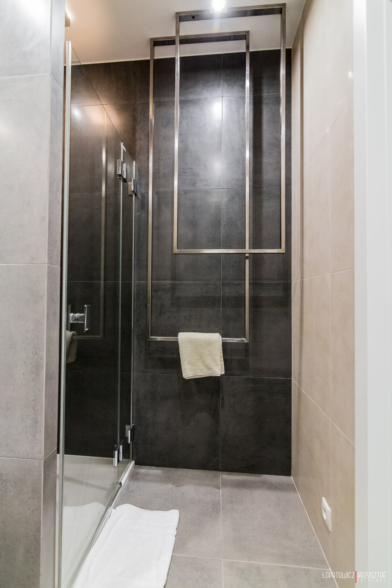 Glass door shower stands next to wall-mounted artistic metal towel holders.