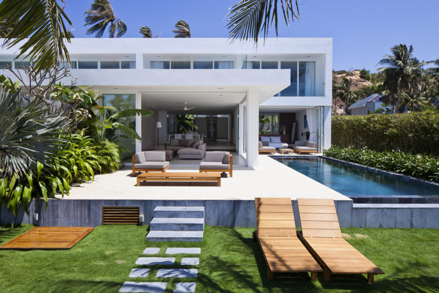 Ocean facing portion extends interior space over this raised patio, with seating on left and infinity pool on right. Stone pathway leads toward beach.