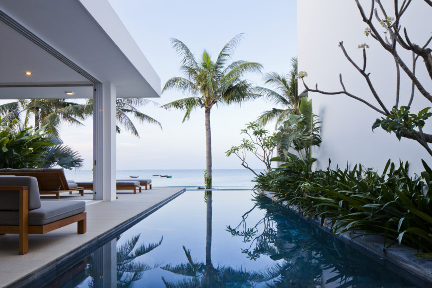 View from one of the bedrooms, overlooking the infinity pool toward the ocean. Rich wood and grey cushioned outdoor furniture sets feature on patio at left.