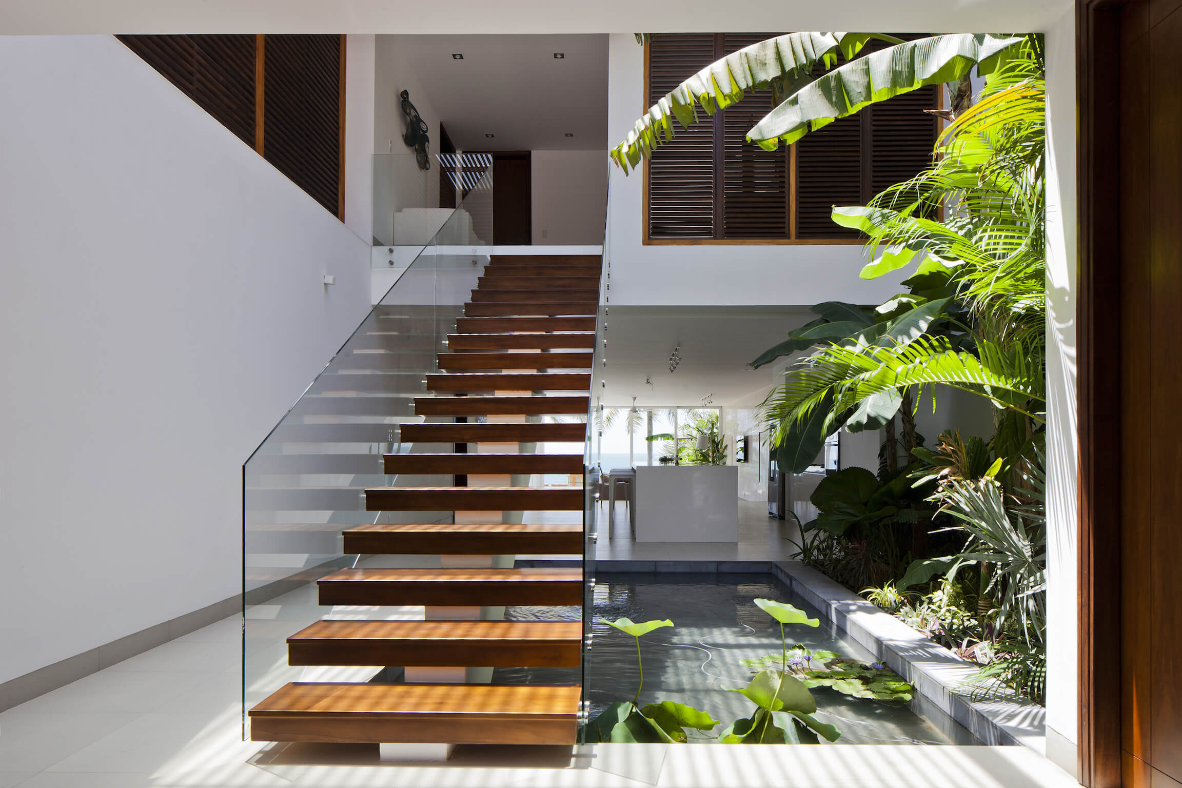 Opposite view in the same home showcases the glass-railing, natural wood staircase and dark louvers on second floor bedrooms.