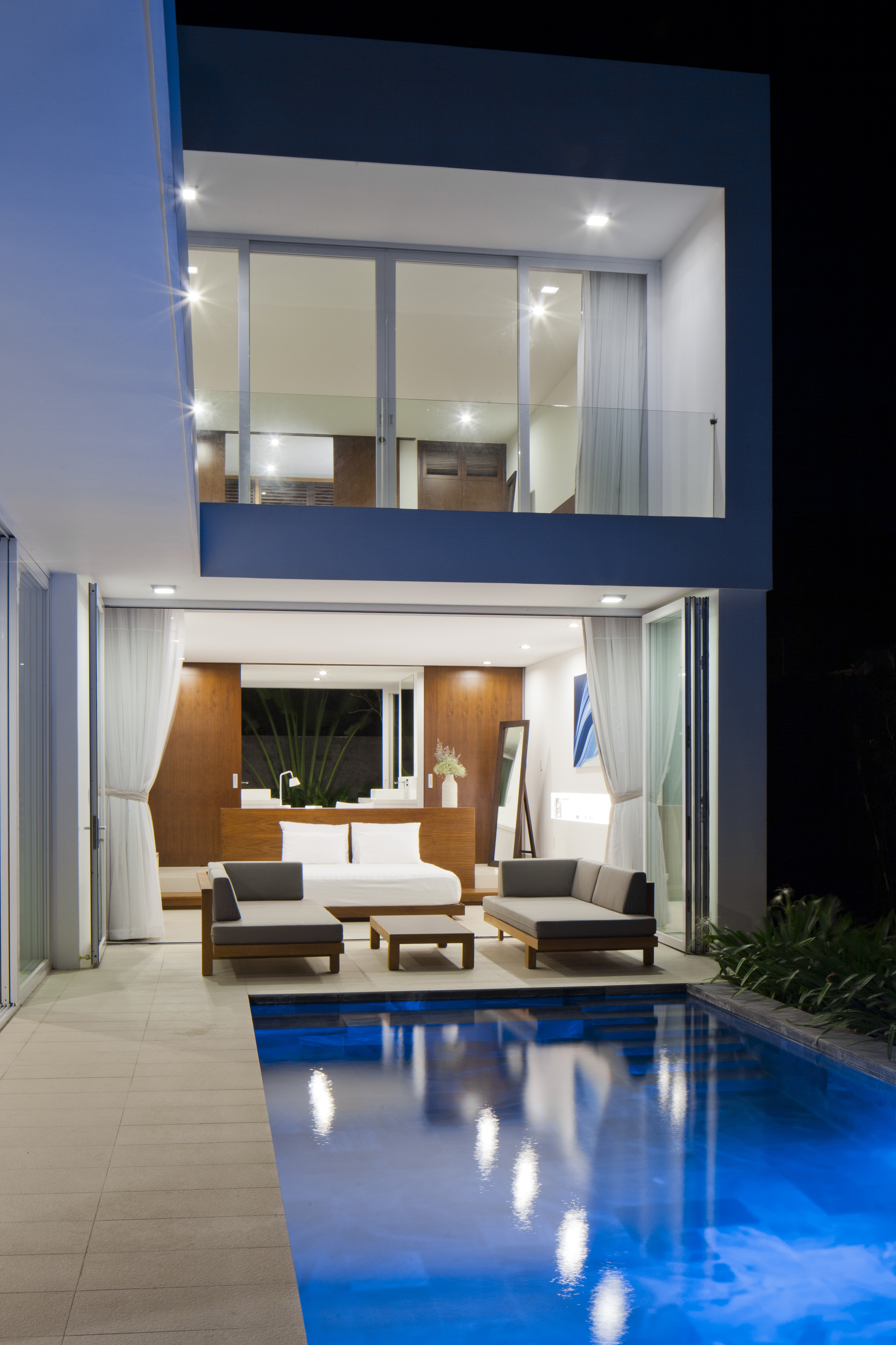 At night, with the interior glowing out over the infinity pool, we see the brilliant white-and-wood contrast in bedrooms, with private, glass-walled balcony overhead.